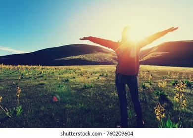 happy woman hiker raised arms  in sunrise mountains
