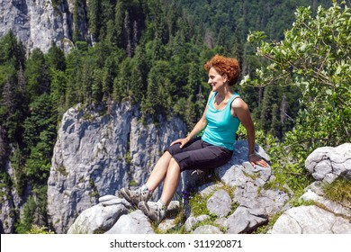 Happy woman hiker sitting on the mountain peak