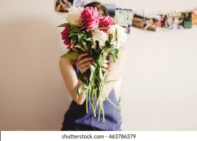 happy woman hipster  holding peony bouquet in front of face sitting on bed in the morning, sweet romantic moment , space for text