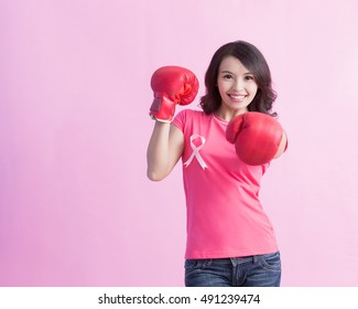 Happy woman hold boxing gloves with pink ribbon ,  prevention breast cancer concept