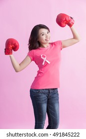 Happy woman hold boxing gloves with pink ribbon , great for prevention breast cancer concept