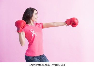 Happy woman hold boxing gloves and look somewhere with pink ribbon , great for prevention breast cancer concept