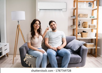 Happy Woman Holding Air Conditioner Remote Control