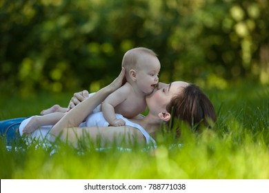 Happy woman holding in arm a baby in a garden and lying on the grass