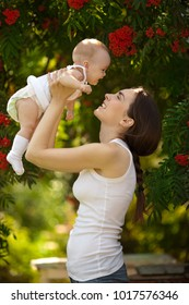 Happy woman holding in arm a laughing baby in a garden. Happy family.