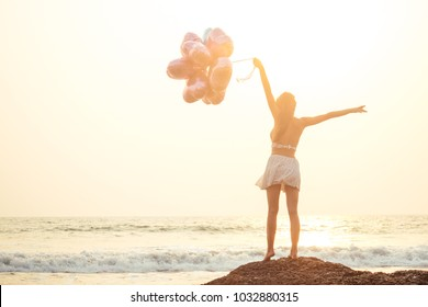 happy woman holding balloons at sea view from back