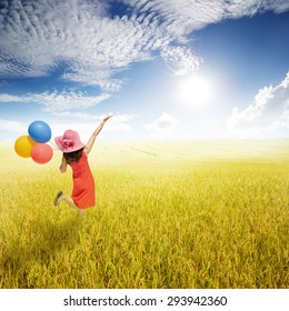 Happy woman holding balloons in yellow rice field and Sun sky.Summer holiday concept.