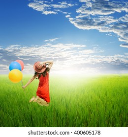 Happy woman holding balloons in yellow rice field and cloud sky.Summer holiday concept.