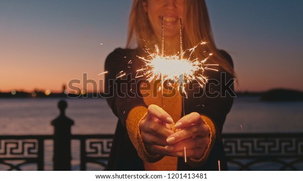 Happy Woman holding bengal lights in outstretchet to camera hands