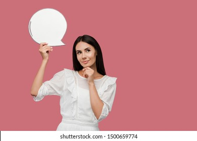 happy woman holding blank speech bubble isolated on pink