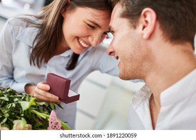 Happy woman holding box with engagement ring after request from man on Valentine's Day