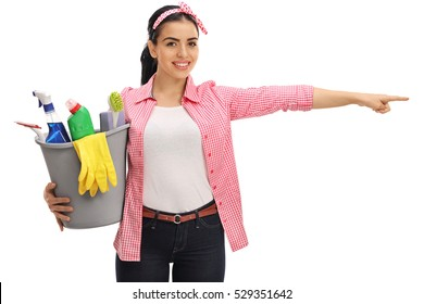 Happy woman holding a bucket filled with cleaning products and pointing right isolated on white background