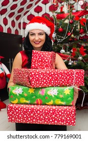 Happy woman holding Christmas presents in front of Xmas tree