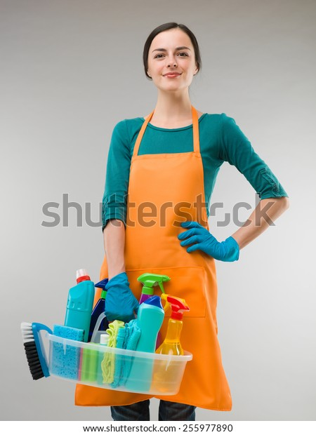 happy woman holding cleaning equipment and looking in front of the camera, on grey background