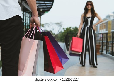 happy woman holding colorful shopping bag outdoors. shopaholic man in city. cheerful shopper enjoy buying. consumerism concept