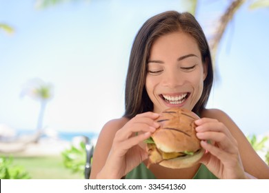 Happy woman holding eating fresh burger sandwich at beach. Young female is sitting at outdoor restaurant. Beautiful tourist is having fresh burger during summer vacation holidays.
