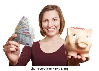 Happy woman holding Euro money bill fan and piggy bank
