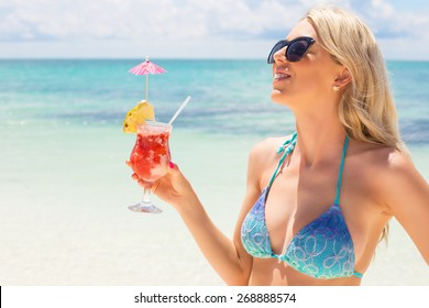 Happy woman holding fresh and tasty cocktail on the beach