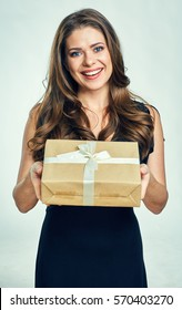 Happy woman holding gift box. Isolated portrait of girl wearing black dress.