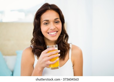 Happy woman holding glass of orange juice while sitting on bed at home
