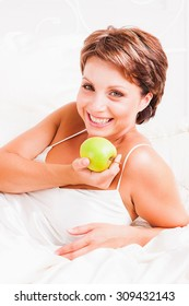 Happy woman holding green apple in her hand while laying in white bed