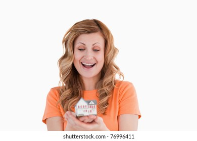 Happy woman holding an house model on a white background