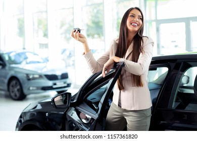 Happy woman holding keys to her new car at the dealership