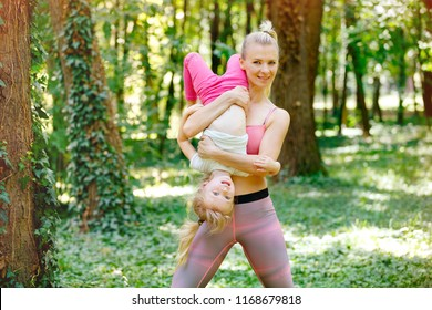 Happy woman holding little girl. Mother and daughter exercise in park and having fun. Happiness, family life