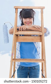 Happy woman holding paint roller leaning on ladder looking at camera