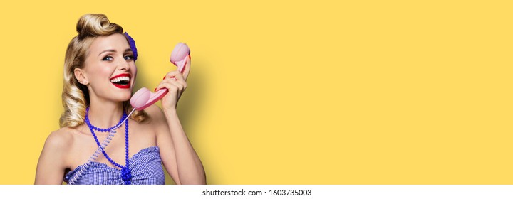 Happy woman holding phone tube. Pin up girl. Retro fashion and vintage concept. Yellow color background. Copy space for some advertise slogan, imaginary or text.