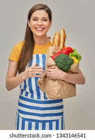 Happy woman holding purchases from grocery store, bread and vegetabless. Isolated studio portrait.
