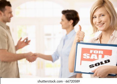 Happy woman holding for sale sign giving the thumb up, smiling man shaking hands with estate agent in background.?
