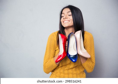 Happy woman holding shoes over gray background