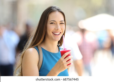 Happy woman holding a slush and looking at you in the street