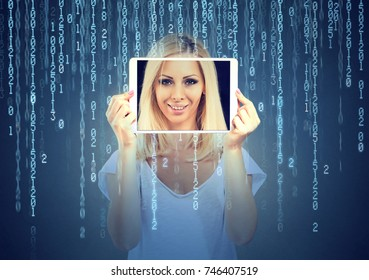 Happy woman holding tablet with her face displayed on a screen isolated on binary code background