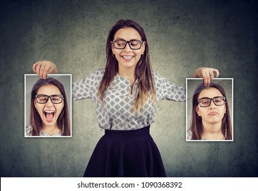 Happy woman holding two different face emotion masks of herself