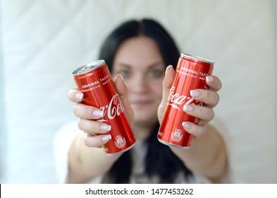 Happy woman holding two non-alcoholic Coca-Cola aluminium tin cans in garage interior
