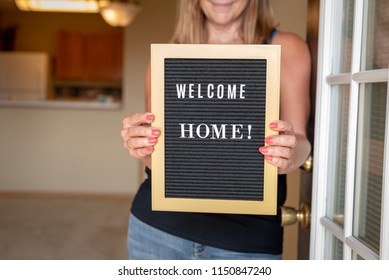 happy woman holding welcome home sign