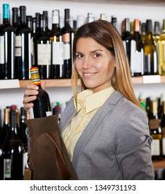 Happy Woman Holding Wine Bottle In Supermarket