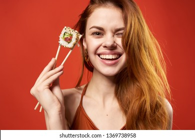 Happy woman holding wooden chopsticks with sushi traditional Japanese food