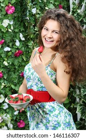Happy woman holds plate with strawberries and brings one berry to mouth in garden.