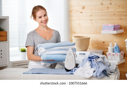 Happy woman housewife ironing clothes iron in laundry at home