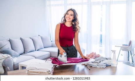 Happy woman housewife ironing clothes iron in laundry at home. Young Smiling Woman Ironing Clothes On  Board At Home. Closeup of woman ironing clothes on ironing board