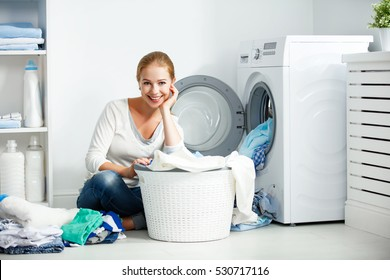happy woman housewife in the laundry room near the washing machine with dirty clothes