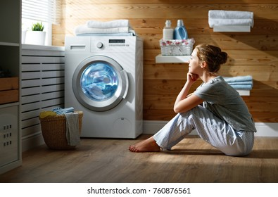 happy woman housewife watching a washing machine in  laundry the evening