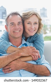 Happy woman hugging her husband on the couch from behind at home in the living room