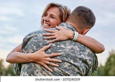 Fröhliche Frau, die seinen Mann umarmte, kam von der Armee zurück. Lächelt fröhliche, kaukasische Freundin, die einen Soldaten umarmt.