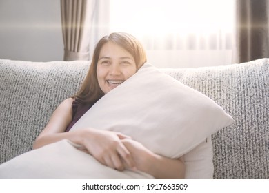 A happy woman hugging a pillow on the sofa on vacation.