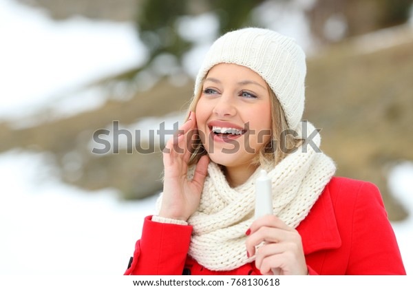 Happy woman hydrating face skin with moisturizer cream in a snowy mountain in winter