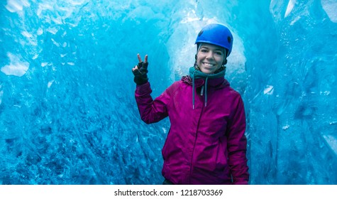 Happy woman inside of a blue ice cave, exploring Vatnajokull National Park with a tour, amazing nature of Skaftafell, Iceland.